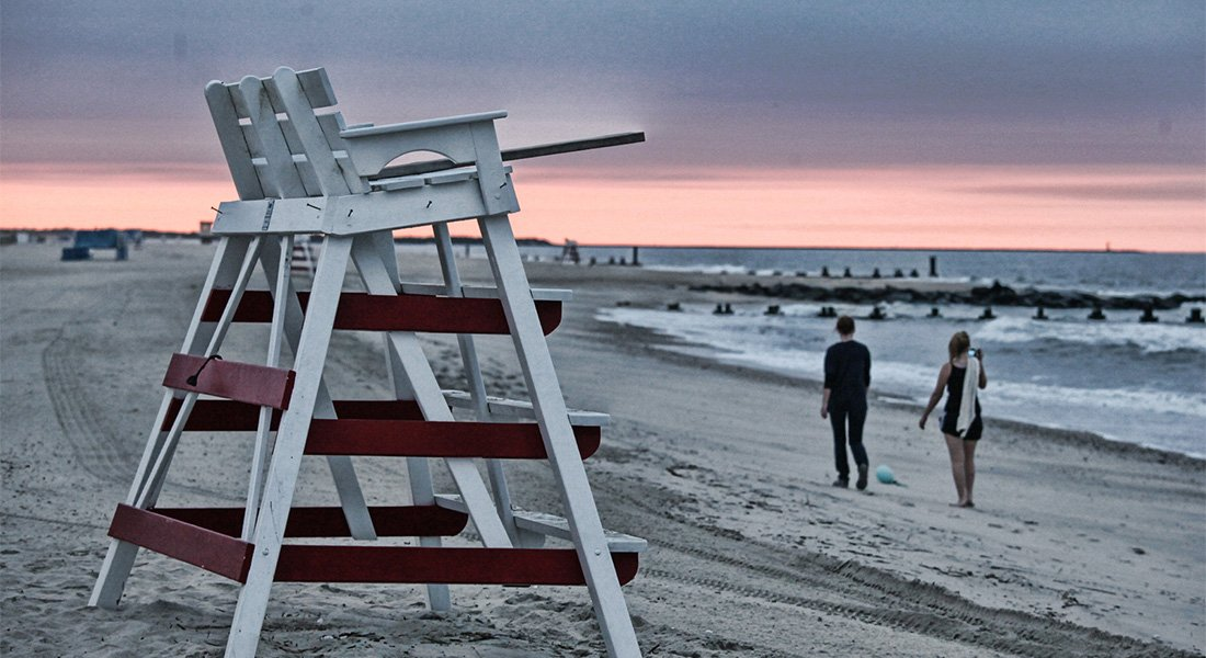 Couple walking near a ooden lifeguard chair on beach at sunset.