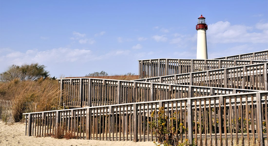 Fenced boardwalk leading to lighthouse on the beach.