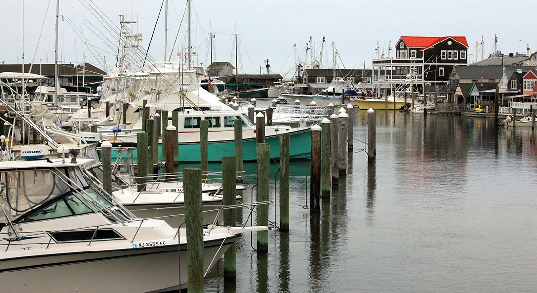 Boats lined up in the harbor docked at pilons.