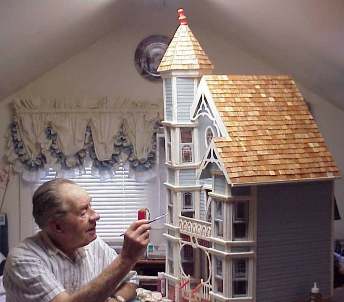 Older gentleman applying paint to a very large Victorian-style dollhouse.