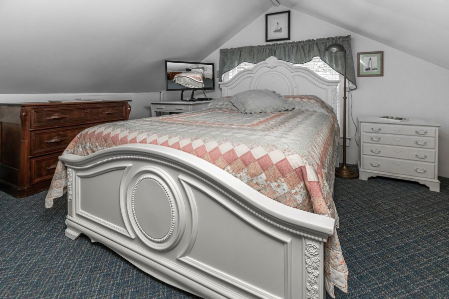 White bed with a colorful quilt in a room with a peaked roof also containing a TV and two dressers.