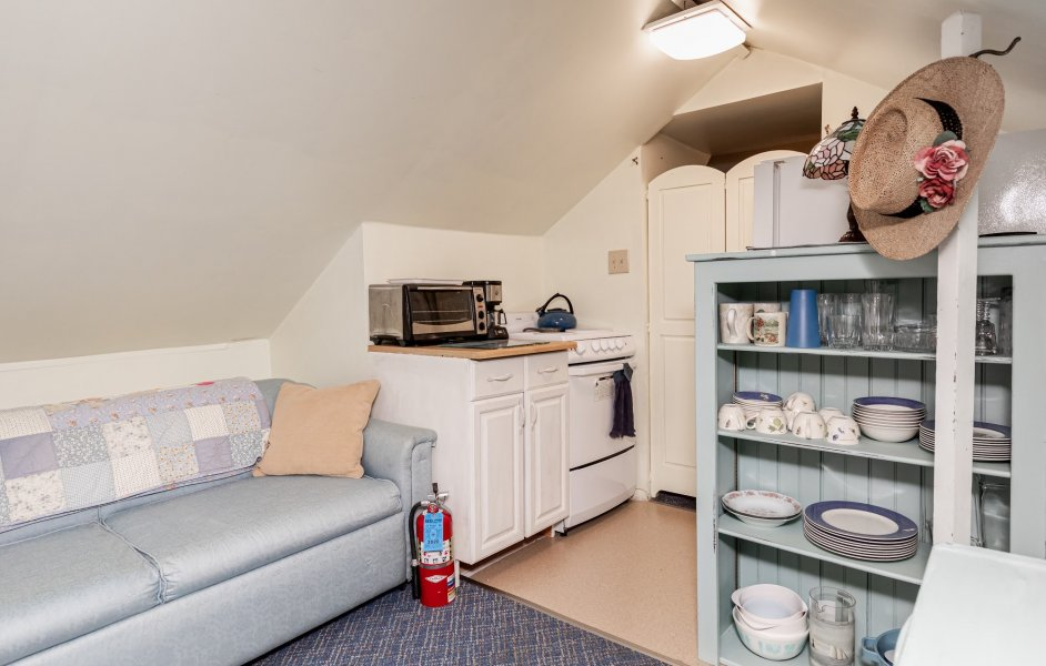 Small kitchenette area fronted by a pale blue sofa and a cabinet with dishware.