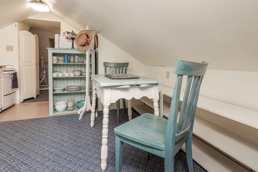 Small table and chairs painted in aqua and white with a kitchenette in the background.