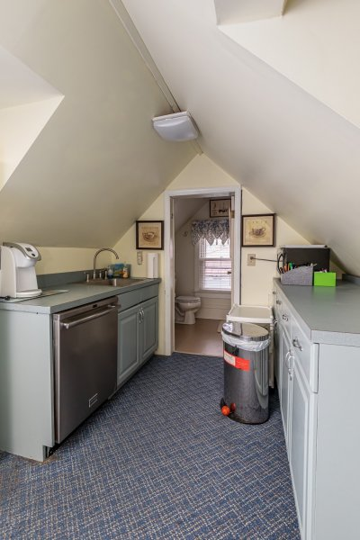 Kitchen in room with a peaked roof, showing a dishwasher, sink and coffee maker.