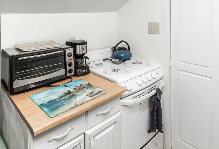Small kitchen with a white stove/oven and a toaster oven and coffee maker on a white cabinet.
