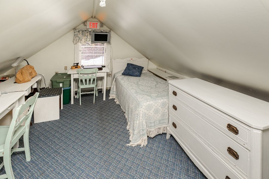 Twin bed with a white coverlet in a peaked-roof room with two white tables with chairs and a white dresser.