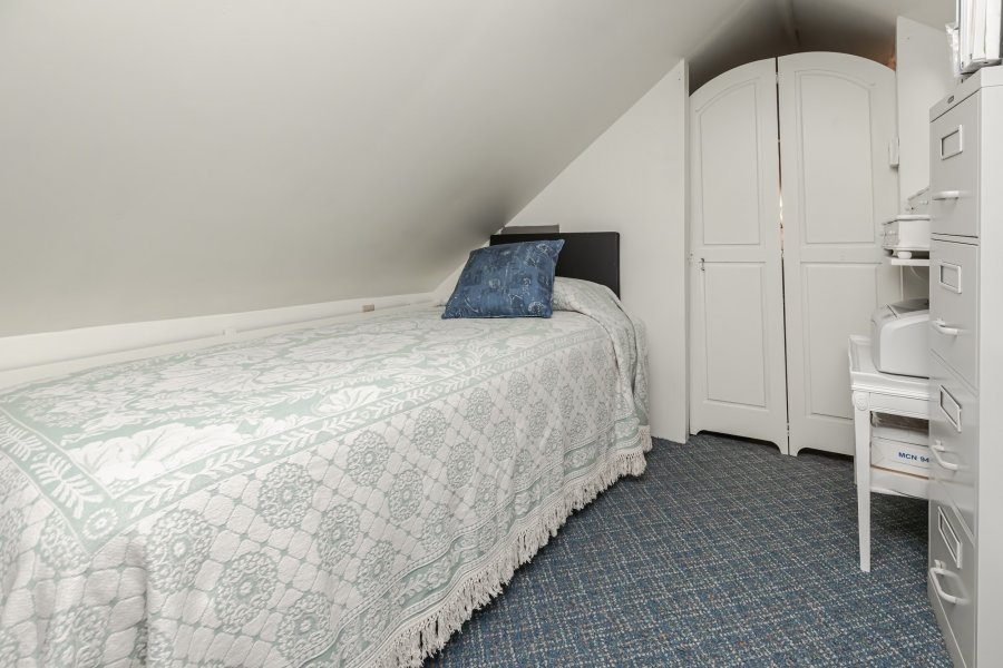 Twin bed with a white coverlet in a peaked-roof room with blue carpet and saloon-style white doors.