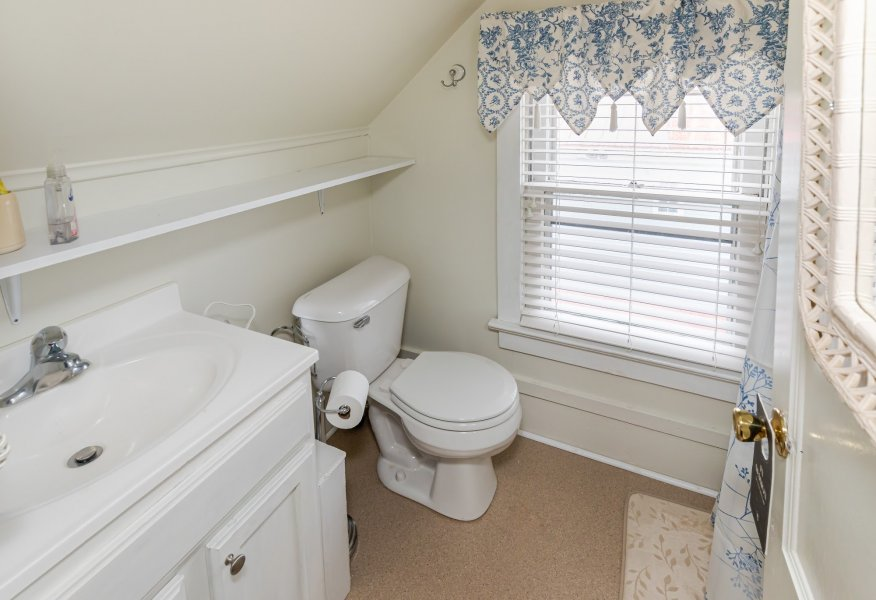 Bathroom with a white sink and toilet and a large window with a blue pattered valance.
