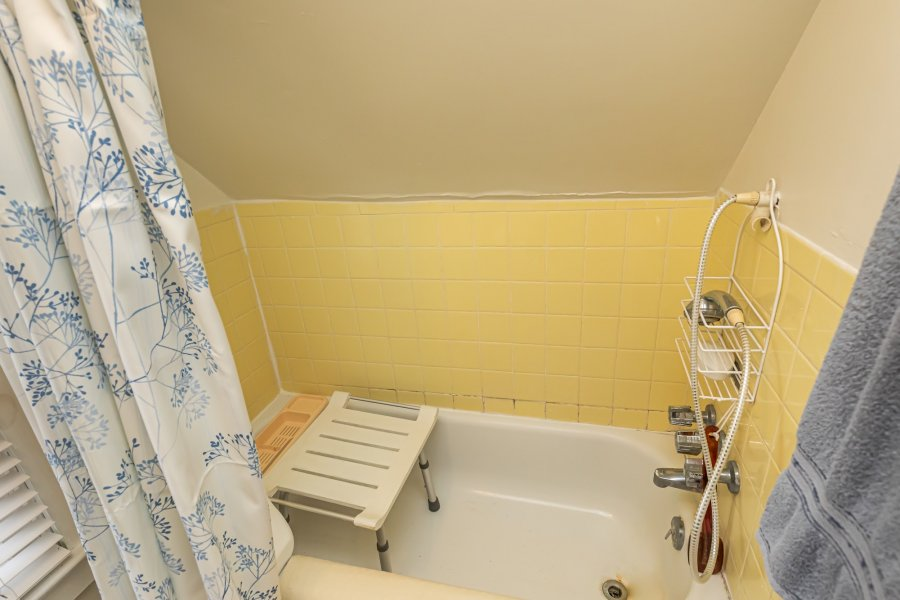 Yellow-tiled bathtub enclosure with a shower head and shower seat.