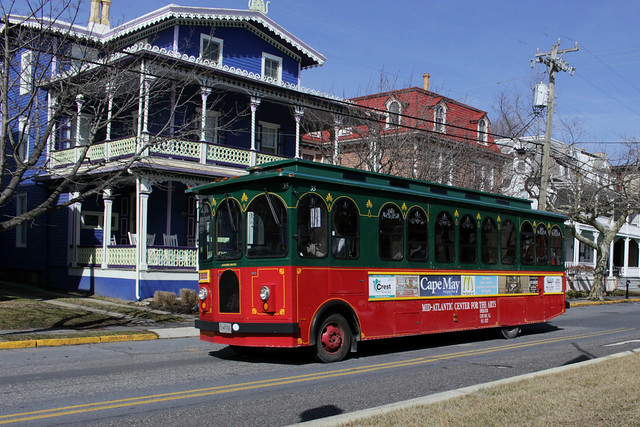Red and green trolley heading down the street in front of blue Victorian house
