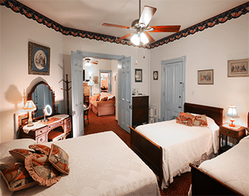 Bedroom with two twin and one queen beds, a mirrored vanity and a ceiling fan.