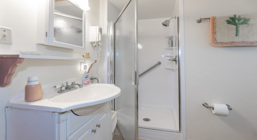 Bathroom with sink cabinet, and mirror next to glass shower door.