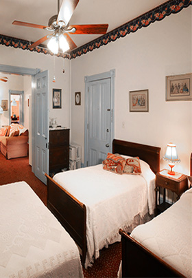Three beds with white blankets in a room with white walls and two blue doors and a brown ceiling fan