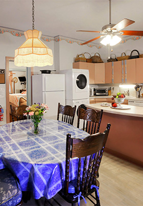 Large full kitchen with dining room table with blue tablecloth and en suite washer and dryer