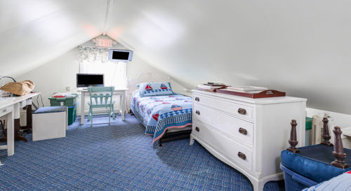 Low ceilings with trundle bed in room with blue accents.