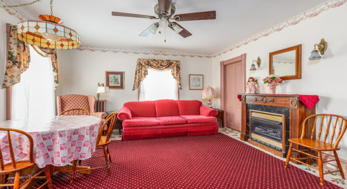View of a red velvet couch with solid wood fireplace hearth and breakfast area