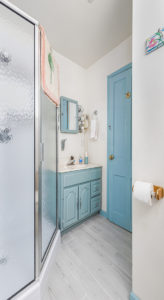Bathroom with blue door and cabinets next to glass shower walls.