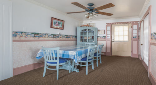 Dining area with blue checkered table cloth in front of curio cabinet in corner.