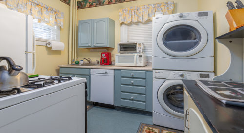 Utility area and kitchen. Stacked washer and dryer next to microwaves and sink, across from range and oven.