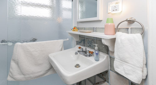 Bathroom with wall mounted sink, underneath mirror and shelf. Obfusced glass shower in background.