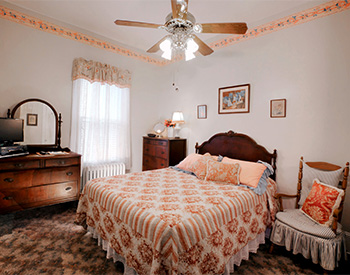 Bedroom with one bed with peach and white cover and a brown dresser and mirror set and one small chair with a light blue cushion