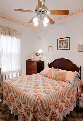 Queen sized bed with peach and white coverlet and ceiling fan above