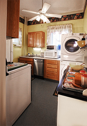 Kitchen with white appliances including a washer and dryer and blue floor