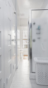 Bathroom shower stall with glass walls. Long view into remainder of bathroom.