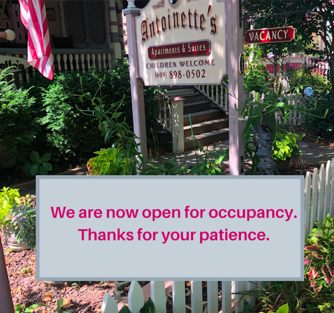 Sign for Antoinette's Apartments & Suites in front of inn with a text box saying, 'We are now open for occupancy. Thanks for your patience'.