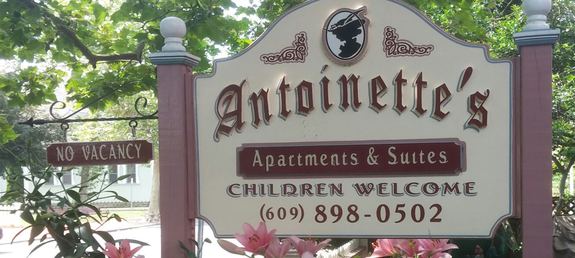 Wooden sign in cream and mauve for Antoinette's Apartments and Suites.
