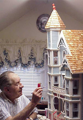 Eldery man painting and constructing a light blue Victorian dollhouse in a white room with Victorian style curtains