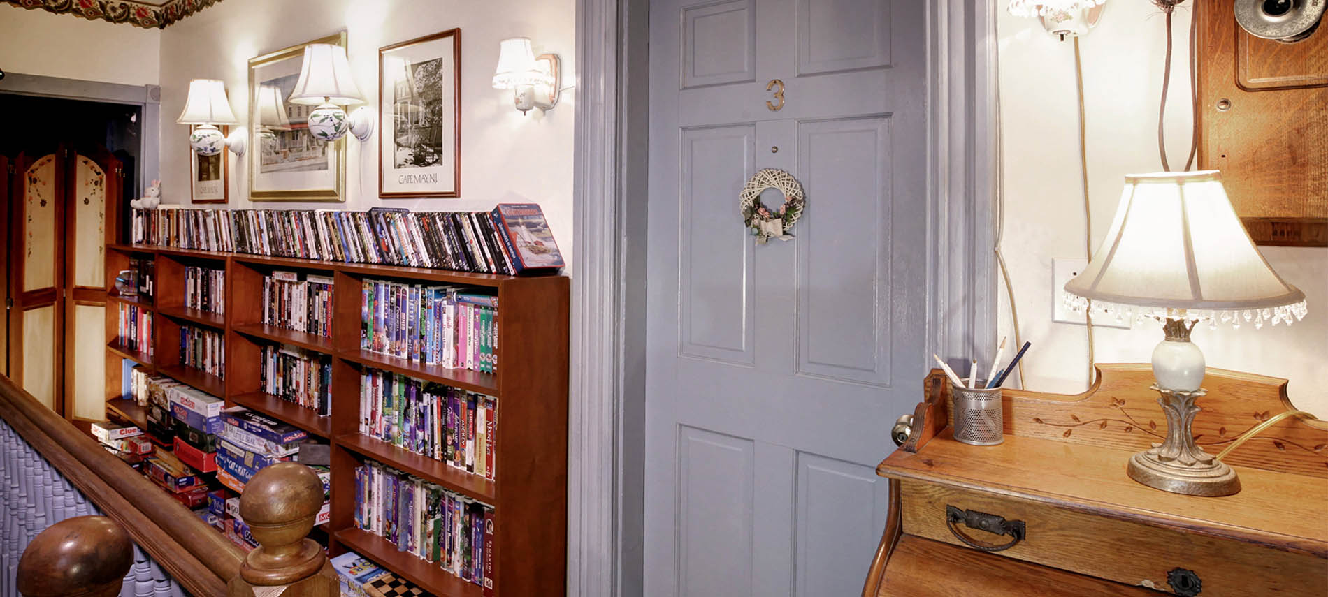 A bookcase packed with books and games in the hallway of a house.