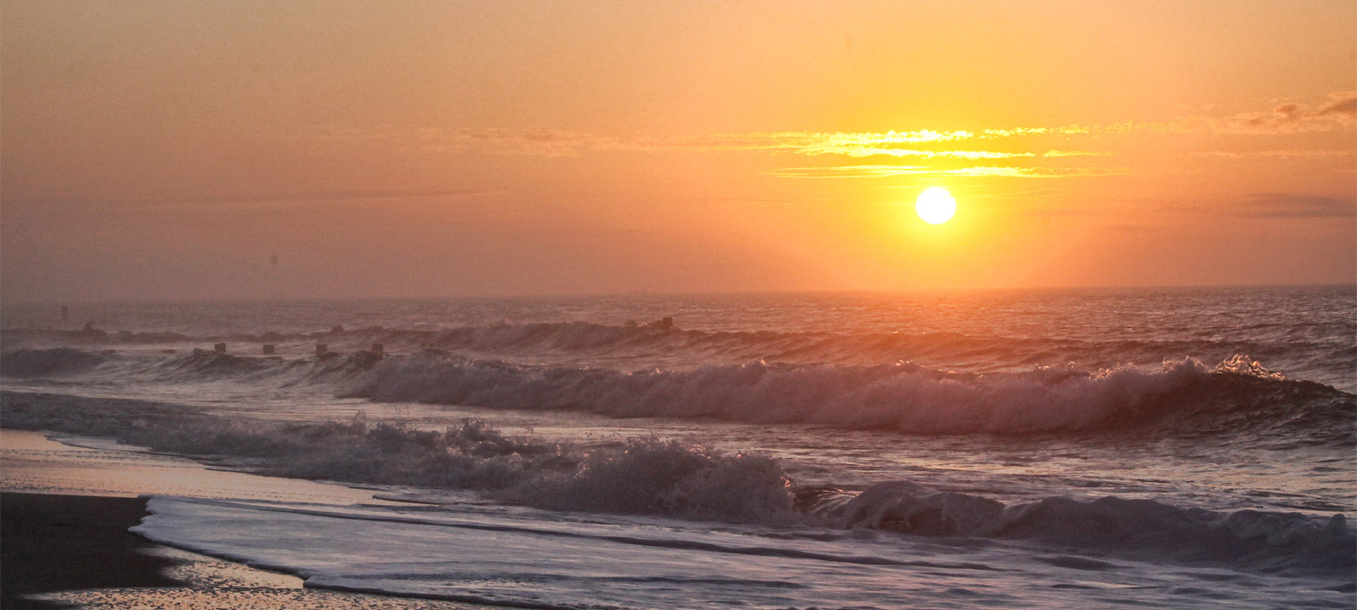 The sun sets in a ball of blazing orange over a restless ocean of waves on the beach.