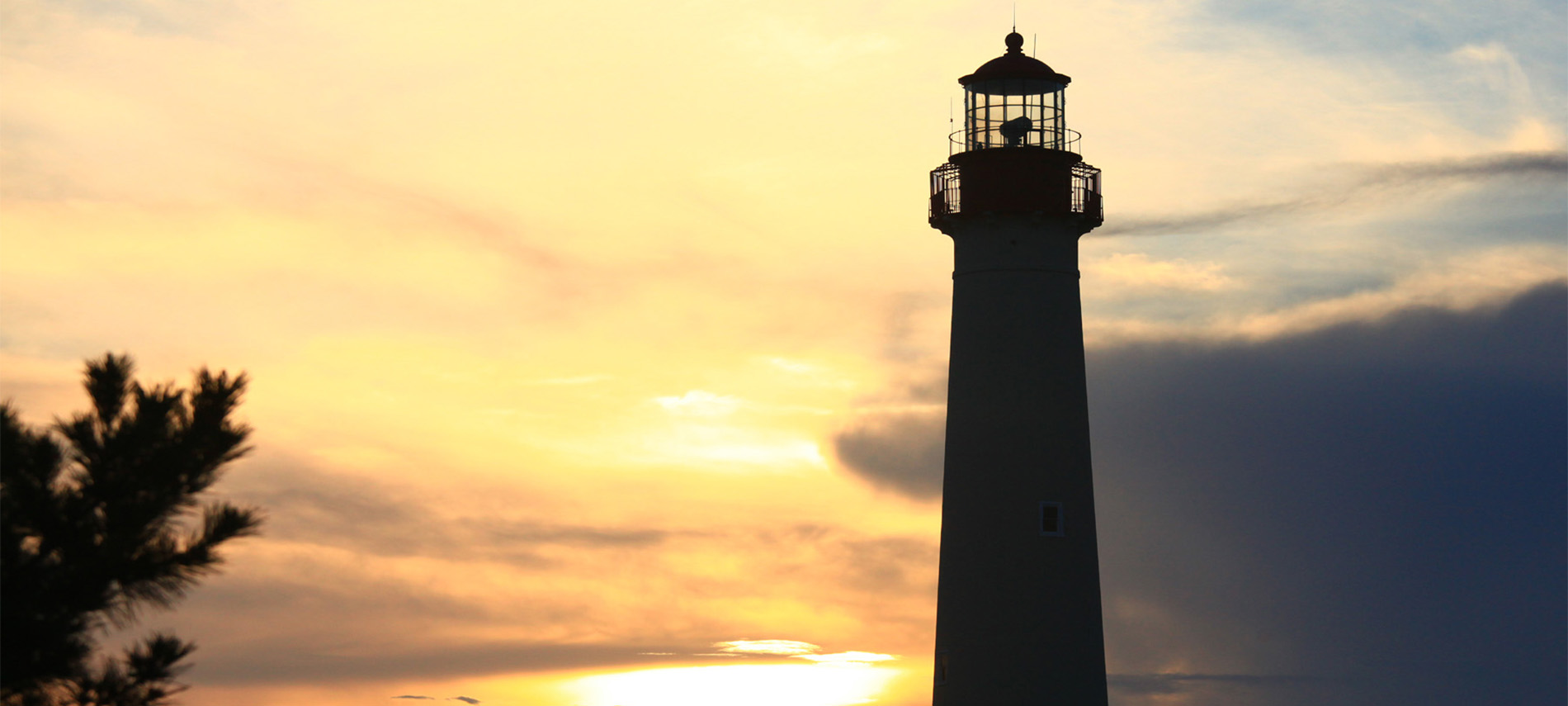 A tall lighthouse cast into shadow by the sunset.