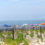 Brightly colored umbrellas dot the shoreline at the beach.
