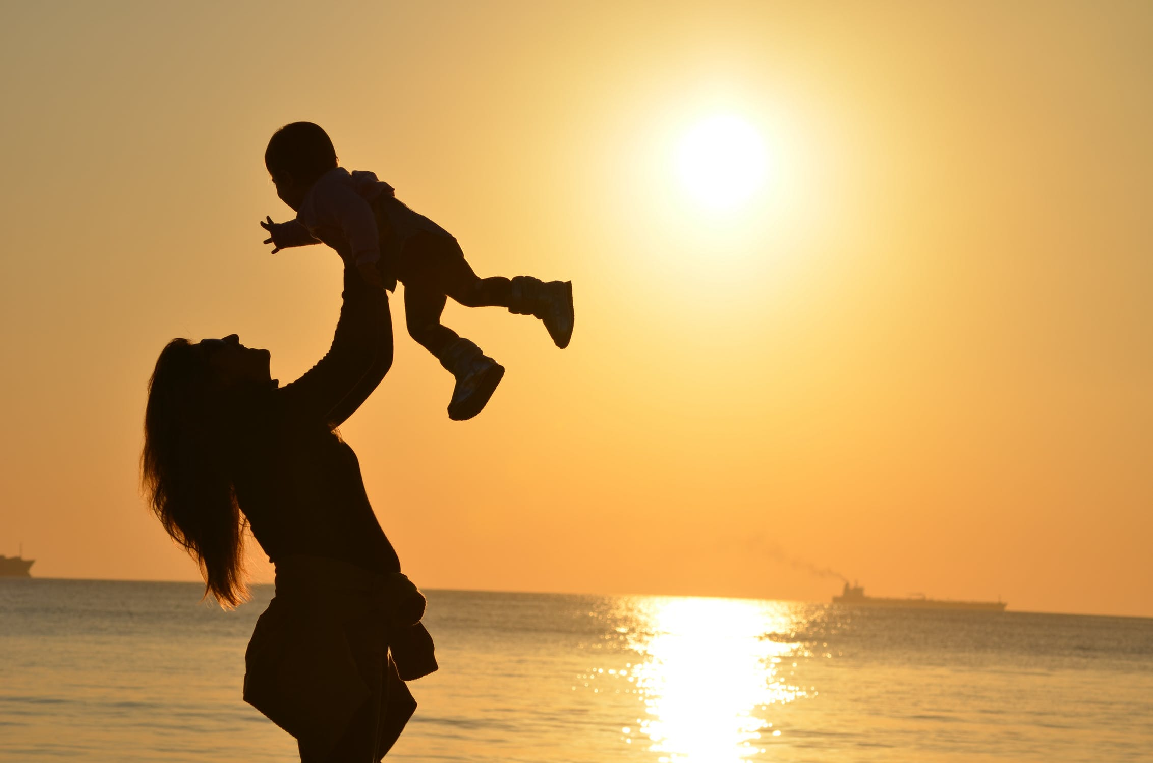 Mother lifting child in joy at the beach at sunset