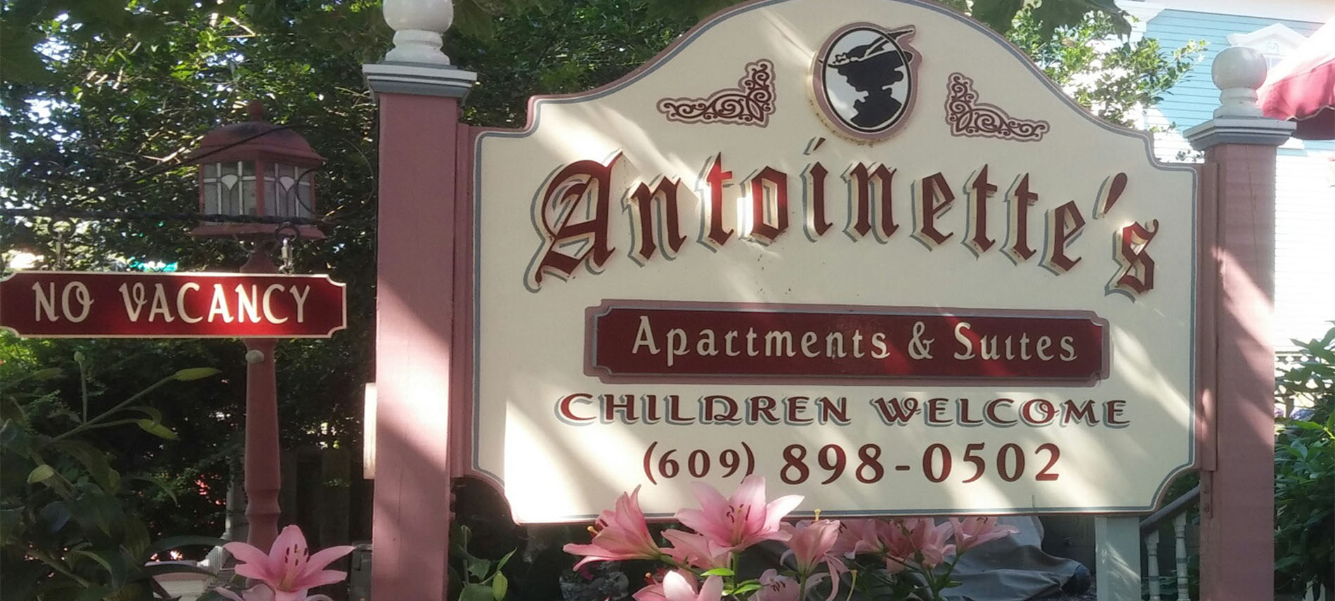 Large mauve and cream exterior sign for Antoinette's Apartments and Suites