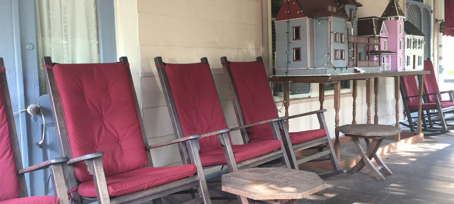 Rocking chairs lined up on a porch with small tables.