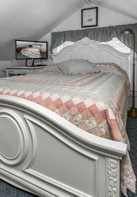 White bed with a colorful quilt in a room with a peaked roof also containing a TV on stand in corner.