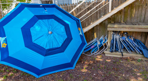 Opened beach umbrella and lawn chairs situated underneath exterior staircase.