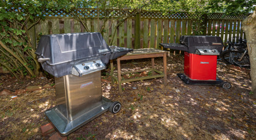 Outdoor cooking area with two gas grills flanking a table.