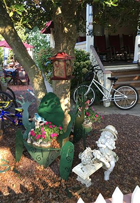 Side yard at the property with two wheel bike in the background and green frog planter in the foreground