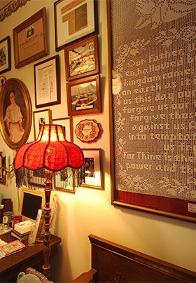 Front lobby with a lamp with red Victorian lampshade and a handmade framed version of the Lord's Prayer